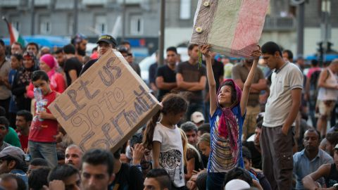 BUDAPEST, HUNGARY - SEPTEMBER 01: A young girl holds up a handmade flag of Afghanistan as migrants protest outside Keleti station in central Budapest after it was closed to migrants earlier today on September 1, 2015 in Budapest, Hungary. The closure was said to be an attempt by the Hungarian government to uphold EU law and restore order after recent choatic scenes at the station. According to the Hungarian authorities a record number of migrants from many parts of the Middle East, Africa and Asia crossed the border from Serbia earlier this week, said to be due in part to the erection of a new fence that is due to be completed at the end of this month. Since the beginning of 2015 the number of migrants using the so-called Balkans route has exploded with migrants arriving in Greece from Turkey and then travelling on through Macedonia and Serbia before entering the EU via Hungary. The massive increase, said to be the largest migration of people since World War II, led Hungarian Prime Minister Victor Orban to order Hungary's army to build a steel and barbed wire security barrier along its entire border with Serbia, after more than 100,000 asylum seekers from a variety of countries and war zones entered the country so far this year. (Photo by Matt Cardy/Getty Images)