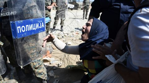 A migrant shouts at Macedonian policemen while trying to cross Greece's northern border into Macedonia. About 1,500 migrants are waiting to cross the border.