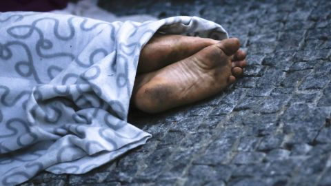 A migrant sleeps on a sidewalk in Berlin near the reception center for refugees and asylum seekers.