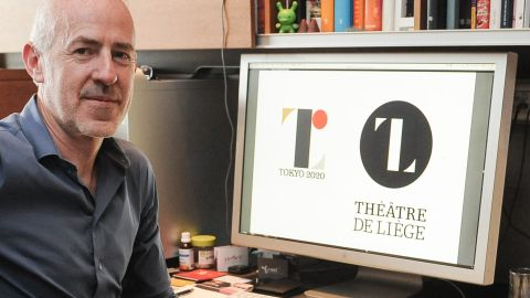 Belgian designer Olivier Debie  poses with Tokyo's 2020 Olympic emblem and the logo of the Theatre de Liege.
