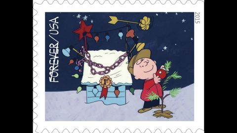 Charlie Brown decorates his tree by the prize-winning lights on Snoopy's doghouse.