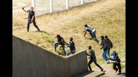 A police officer in Calais, France, tries to prevent migrants from heading for the Channel Tunnel to England in June 2015.