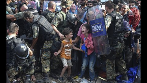 """Children cry as migrants in Greece try to break through a police cordon to cross into Macedonia in August 2015. Thousands of migrants -- most of them fleeing Syria's bitter conflict -- were stranded in a <a href=""""http://www.cnn.com/2015/08/22/europe/europe-macedonia-migrant-crisis/"""" target=""""_blank"""">no-man's land</a> on the border."""