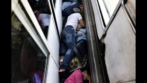 """Syrian refugees sleep on the floor of a train car taking them from Macedonia to the Serbian border in August 2015. <a href=""""http://www.cnn.com/2015/08/28/world/iyw-migrant-how-to-help/index.html"""" target=""""_blank"""">How to help the ongoing migrant crisis</a>"""