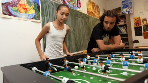 Eleven-year-old Serbian refugee Kristina (L) is pictured playing table football, or foosball, with Iranian refugee Andabili Hossein at a temporary home providing assistance for refugees on August 5, 2015 in Berlin, Germany.