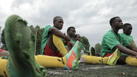 """Malian refugee Aboudala Dembele (C), rests with teammates at half-time during the match against Guinea as part of the """"Balon Mundial"""" football tournament for migrants and foreigners, on June 13, 2015 in Turin."""