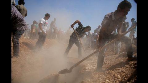 Men dig graves for the three coffins in Kobani on September 4, 2015.