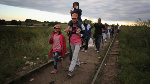 Migrants and refugees cross the border from Serbia into Hungary along the railway tracks close to the village of Roszke on September 6.