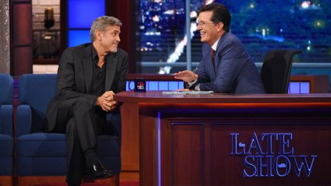 """Stephen Colbert, right, talks with actor George Clooney during the premiere episode of """"The Late Show,"""" Tuesday Sept. 8, 2015, in New York. Clooney and Republican presidential candidate Jeb Bush were the guests for Colbert's debut. (Jeffrey R. Staab/CBS via AP)"""