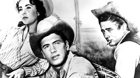 """Hudson scored his only Oscar nomination as Bick Benedict in the 1956 epic """"Giant,"""" with Elizabeth Taylor as his wife and James Dean, right, as his rival. He played a stubborn cattle rancher battling change in oil-rich Texas in the George Stevens film based on Edna Ferber's novel. Taylor, a good friend, later became a passionate AIDS activist. A year after """"Giant,"""" Hudson topped the <a href=""""https://tbmovielists.wordpress.com/quigleys-top-ten-box-office-champions-by-year/"""" target=""""_blank"""" target=""""_blank"""">list of box-office stars in America</a>. He continued to appear in the Top 10 through 1964."""