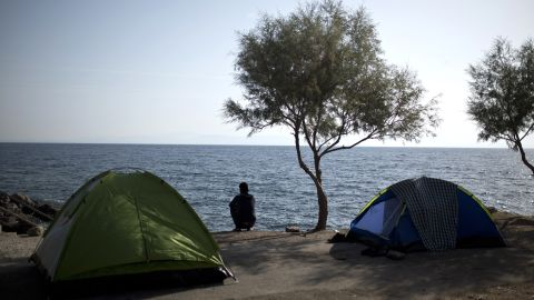 Migrants buy tents to make their journey more comfortable. A Facebook page for refugees even tells them what sort to buy and where. Here, a migrant looks out to sea.