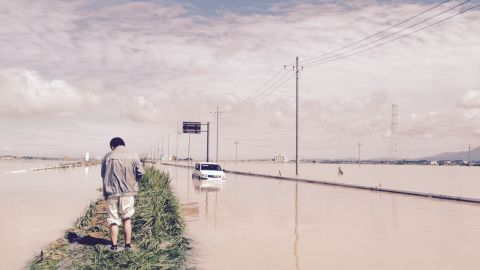 Shigeru Kikuchi attempted to drive along a flooded road but found himself stranded after his car became completely waterlogged.