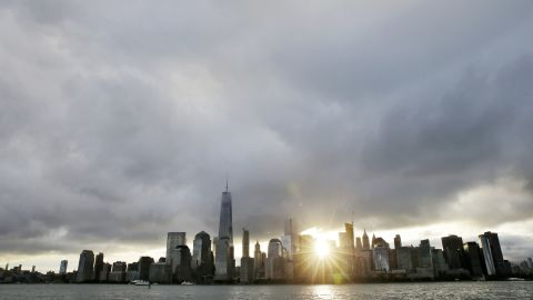 The sun rises, as One World Trade Center, center left, stands on the 14th anniversary of the Sept. 11, 2001 terrorist attacks, Friday, Sept. 11, 2015, in Jersey City, N.J. Victims' relatives began marking the 14th anniversary of Sept. 11 in a subdued gathering Friday at ground zero, with a moment of silence and somber reading of names. (AP Photo/Mel Evans)