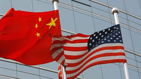 """Beijing, CHINA: A US and a Chinese flag wave outside a commercial building in Beijing, 09 July 2007. US Secretary of State Condoleezza Rice 06 July 2007 accused China of flouting the rules of global trade in its headlong economic expansion as the US administration """"has not been hesitant"""" to deploy trade tools against China, including a complaint lodged with the World Trade Organization over copyright piracy. AFP PHOTO/TEH ENG KOON (Photo credit should read TEH ENG KOON/AFP/Getty Images)"""