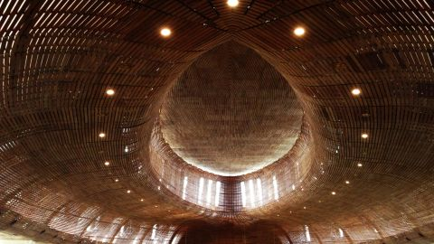"""This church's design is made of three concentric ovals and its warm, intimate interior is lined with timber. Teak wood slats are horizontally secured onto steel frames. Director of the Indonesian branch of Denton Corker Marshall, Budiman Hendropurnomo says the use of these materials and structure of design are intended to create acoustics that """"would have the likeness of singing inside a violin."""""""