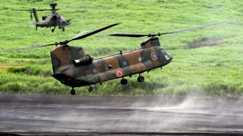 A CH-47J Chinook heavy lift helicopter, escorted by an AH-64DJP Apache attack helicopter (top L), prepares to land Japanese Ground Self-Defense Force troops during an annual live fire exercise at the Higashi-Fuji firing range in Gotemba, at the foot of Mount Fuji in Shizuoka prefecture on August 18, 2015. The annual drill involves some 2,300 personnel, 80 tanks and armoured vehicles and some 20 aircraft and helicopters.   AFP PHOTO / Toru YAMANAKA        (Photo credit should read TORU YAMANAKA/AFP/Getty Images)