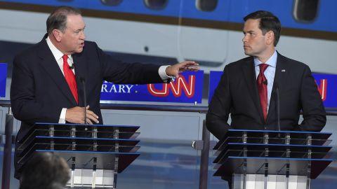 Rubio looks on as Huckabee speaks.