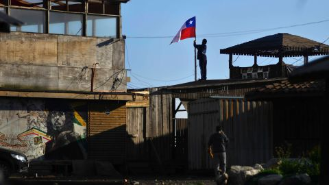A man secures a Chilean flag on a roof after an earthquake-triggered tsunami damaged homes and businesses in Concon, Chile, Thursday, Sept. 17, 2015. Several coastal towns were flooded from small tsunami waves set off by late Wednesday's magnitude-8.3 earthquake, which shook the Earth so strongly that rumbles were felt across South America. (AP Photo/Matias Delacroix) CHILE OUT - NO USAR EN CHILE