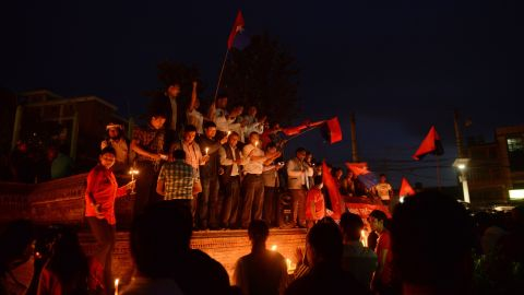 Nepalese youths hold candles and sing as they celebrate Nepal's new national constitution in Kathmandu on September 17, 2015, work on which began in 2008.