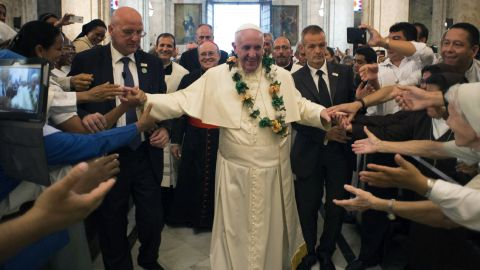 In this photo taken on Sunday, Sept. 20, 2015, Pope Francis is greeted by faithful as he enters the San Cristobal Cathedral, Havana, Cuba. Francis presided over the evening prayer service in Havana's 18th century cathedral, where he broke from prepared remarks and spoke off-the-cuff at length for the first time during his trip to Cuba. (L'Osservatore Romano/Pool Photo via AP)