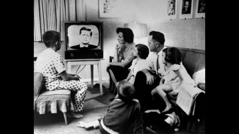 """A family gathers around a television to watch the debate. More than 66 million people watched out of a population of about 180 million. """"I don't think it's overstating the fact that, on that date, politics and television changed forever,"""" said Bruce DuMont, a nationally syndicated radio talk show host and president of the Museum of Broadcast Communications. """"After that debate, it was not just what you said in a campaign that was important, but how you looked saying it."""""""