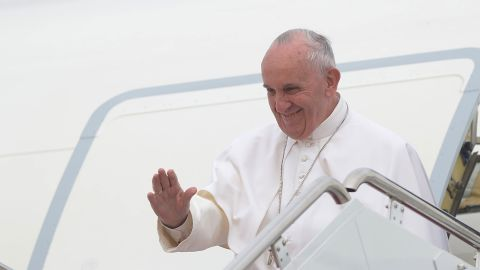 Pope Francis waves towards US President Barack Obama and his family as he steps off his plane upon arrival at Andrews Air Force Base in Maryland.