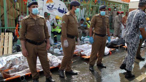 Saudi emergency personnel stand near bodies of Hajj pilgrims.