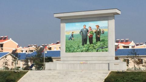 """A large mural of North Korean founder Kim Il Sung stands outside the Jang Chon cooperative farm, a 30-minute drive outside the capital Pyongyang. <a href=""""http://www.cnn.com/2015/09/25/asia/north-korea-most-famous-farmer/"""">CNN visited the farm in September 2015.</a>"""
