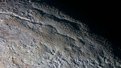 """These photos show Pluto's variety of textures, including what NASA calls """"rounded and bizarrely textured mountains."""" The mountains are informally called the Tartarus Dorsa. This image shows about 330 miles (530 kilometers) of Pluto's terrain. It combines blue, red and infrared images taken by the space probe's Ralph/Multispectral Visual Imaging Camera. The images were taken on July 14, during the probe's flyby. They were released on September 24."""