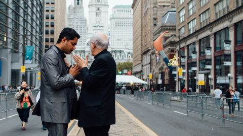 A priest blesses a Catholic man on the way to see Pope Francis speak.