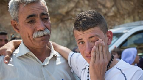 Sabah Mirza Mahmoud, right, cries next to his uncle Jamil Jato as Mahmoud and his sisters prepare to leave for Germany.