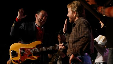 """Republican Presidential hopeful and former Arkansas Governor Mike Huckabee high-fives with actor Chuck Norris during a """"Chuck and Huck"""" rally January 1, 2008 in Des Moines, Iowa."""