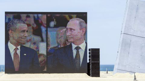 """Obama and Putin share a comical and awkward moment on a large split-screen during an international ceremony on the stretch code-named Sword Beach, in Ouistreham, France, to commemorate the Allied invasion of Normandy on June 6, 2014. Obama and Putin had an informal 15-minute chat during lunch at the ceremony that marked the 70th anniversary of the D-day landings. """"It's a positive thing that they spoke, but more needs to be done,"""" a senior U.S. official said at the time."""