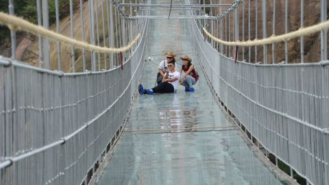 PINGJIANG, CHINA - SEPTEMBER 24:  (CHINA OUT) Tourists take a selfie on a suspension bridge made of glass at the Shiniuzhai National Geological Park on September 24, 2015 in Pingjiang County, China. The 300-meter-long glass suspension bridge, with a maximum height of 180 meters, opened to the public on Thursday.  (Photo by ChinaFotoPress/ChinaFotoPress via Getty Images)