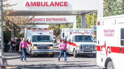 Paramedics return to their ambulances after delivering patients to Mercy Medical Center in Roseburg, Ore., following a deadly shooting at Umpqua Community College, in Roseburg, Thursday, Oct. 1, 2015. (Aaron Yost/Roseburg News-Review via AP)