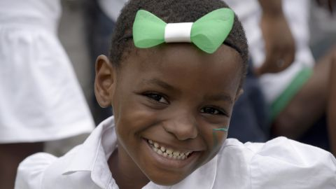 """A pupil smiles as she wears on her forehead a green and white bow tie, the colors of Nigeria, on October 1, 2015  as part of Nigeria's independence anniversary celebrations, in Lagos. Nigeria's President Muhammadu Buhari on Thursday called for an end to """"unruly behaviour"""" in the country, saying progress could not happen without a change in citizens' attitudes. The call, made in his first Independence Day address as civilian president, will likely remind some of his time as military ruler in the 1980s, when he cracked down on so-called """"indiscipline"""". AFP PHOTO / PIUS UTOMI EKPEI        (Photo credit should read PIUS UTOMI EKPEI/AFP/Getty Images)"""