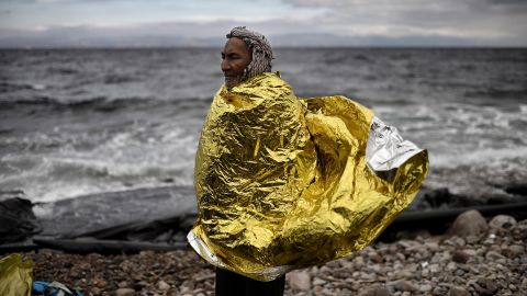 A man with a protective blanket wrapped around him stands on the shore of Lesbos, Greece, as refugees and migrants arrive after crossing the Aegean Sea from Turkey on Wednesday, September 30.