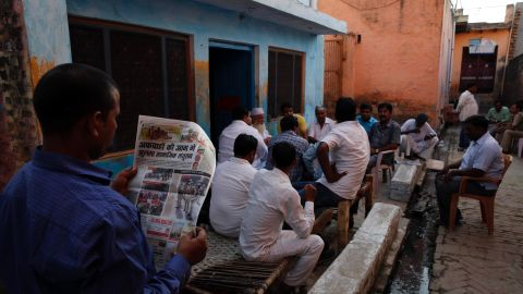A relative of Mohammad Akhlaq reads about the killing in a newspaper in Bisara on September 30.
