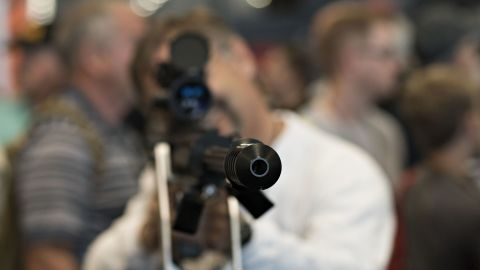 An attendee looks through the scope of a rifle at the 144th National Rifle Association (NRA) Annual Meetings and Exhibits at the Music City Center in Nashville, Tennessee, U.S., on Friday, April 10, 2015. Top Republican contenders for their party's 2016 presidential nomination are lining up to speak at the annual NRA event, except New Jersey Governor Chris Christie and Kentucky Senator Rand Paul who were snubbed by the country's largest and most powerful gun lobby. Photographer: Daniel Acker/Bloomberg via Getty Images