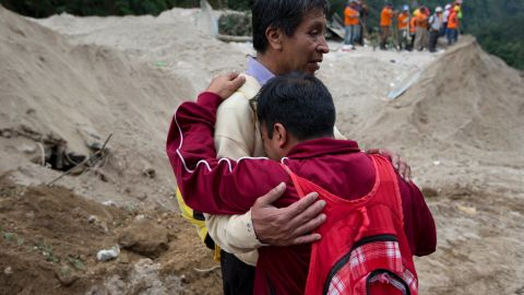 Neighbors comfort each other as rescue workers continue the search for townspeople on October 3.