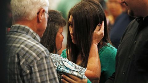 Lacey Scroggins, center right, is comforted during a church service at the New Beginnings Church of God, Sunday, October 4, in Roseburg, Ore. Scroggins is a survivor of the shooting at Umpqua Community College.