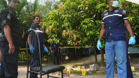 Bangladeshi police officials stand guard at the site where a Japanese citizen was shot to death by attackers in Rangpur on October 3, 2015.