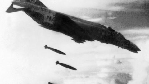 A U.S. F4 Phantom drops bombs over a Viet Cong controlled area in South Vietnam in November 1965 during the Vietnam War.