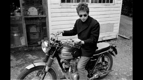 """Suddenly, Dylan became a name. He performed at the 1963 March on Washington; his song """"Blowin' in the Wind"""" was covered by Peter, Paul & Mary and became a Top Five hit. He was in demand. He started retreating to Woodstock, New York, a haven for artists since the early 20th century and where his manager, Albert Grossman, had a home. Dylan is pictured here on a Triumph motorcycle behind the town's Cafe Espresso in 1964."""