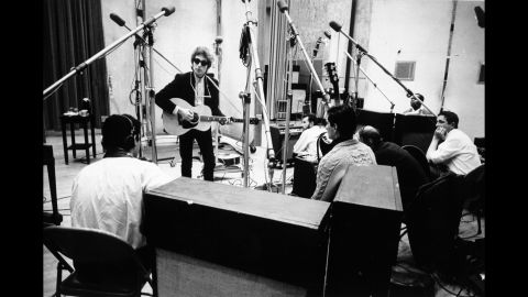 """Dylan's early work was in more traditional folk and protest veins, but he started looking inward with 1964's """"Another Side of Bob Dylan."""" His lyrics, in particular, became more imagistic. In early 1965, he started work on a new album, """"Bringing It All Back Home."""" In some cases, the songs were accompanied by a full rock band. Dylan is shown here at the beginning of the """"Back Home"""" sessions with guitarist Kenny Rankin, left, and other musicians at Columbia's Studio A in New York."""