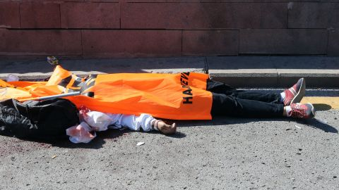 The body of a victim is covered with a flag.