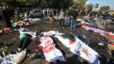 Bodies lie covered with flags and banners at the blast site.
