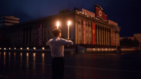 A volunteer holds burning torches at Kim Il Sung Square.