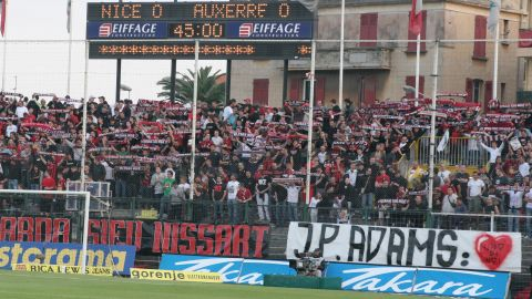 """Nice fans display a banner reading """"J-P Adams: One of Us"""" on April 28, 2007, ahead of their former player's sons -- Laurent and Frédéric -- symbolically kicking off a match against Auxerre in tribute to their father."""