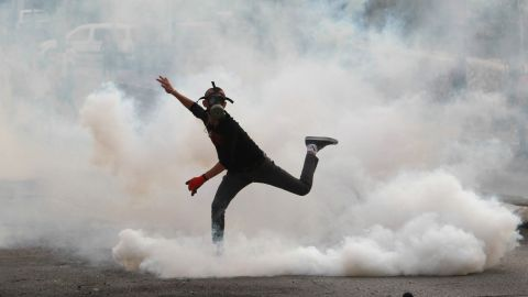 A Palestinian protester in Bethlehem throws a tear-gas canister back at Israeli security forces on October 12.